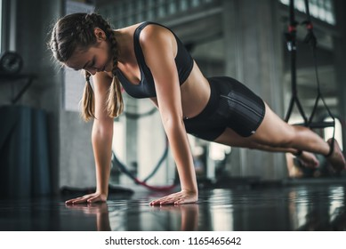 Cinematic tone of young attractive fitness woman exercise with machine in gym. Individual sport to fit muscles of body for healthy life concept.