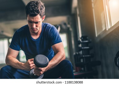 Cinematic tone of young attractive fitness man exercise with machine and dumbbell in gym. Individual sport to fit muscles of body for healthy life concept.