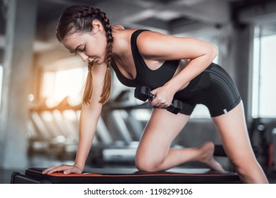 Cinematic tone of young attractive fitness woman exercise with dumbbell in gym. Individual sport to fit muscles of body for healthy life concept.