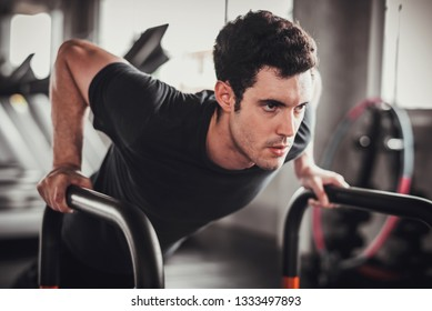 Cinematic tone of young attractive fitness man exercise with machine in gym. Individual sport to training and fit muscles of body for healthy life concept.