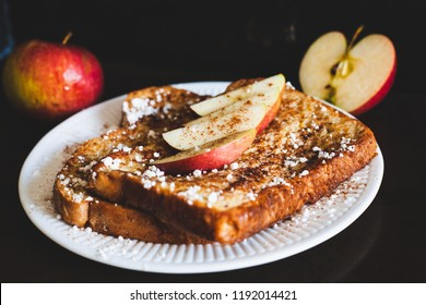 Cinnamon apple french toast with confectioner sugar on a white plate with dark background