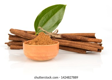 Cinnamon bark, green leaves and powder on a white background.