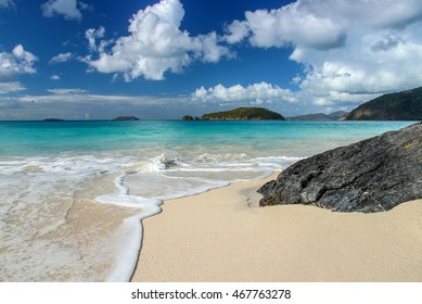 Cinnamon Bay, St John, US Virgin Islands.  Puffy white clouds hang in the bright blue sky over the turquoise waters of the Caribbean sea as the gentle waves kiss the sand.