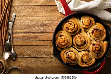 Cinnamon buns with chocolate chips baked in a cast iron pan overhead shot