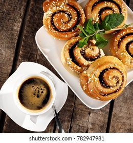 Cinnamon buns with coffee on wood, close up, top view
