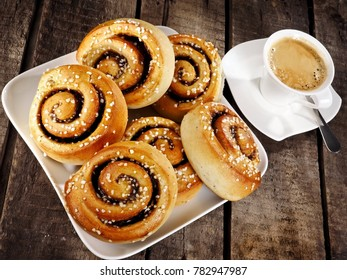 Cinnamon buns with coffee on wood