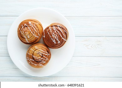 Cinnamon buns in plate on wooden table