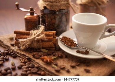 Cinnamon  with coffee beans and white cup on a wooden board
