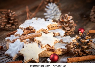 Cinnamon cookies for christmas on wooden table decorated with pine cones and christmas balls
