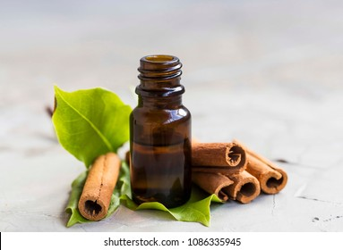 Cinnamon essential oil bottle with cinnamon sticks and leaves, aromatherapy oil