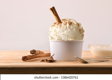 Cinnamon ice cream decorated with cinnamon sticks on a wooden table. Horizontal composition. Front view.