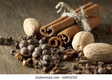 Cinnamon, nutmeg, allspice and cloves on wooden background.