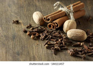 Cinnamon, nutmeg and cloves on wooden background.