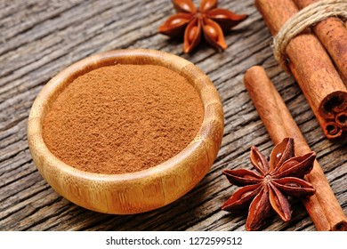 Cinnamon powder in a bamboo bowl with star anise and cinnamon sticks on a wood table