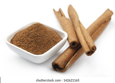 Cinnamon and Cinnamon Powder in a ceramic Bowl. isolated on a white background.