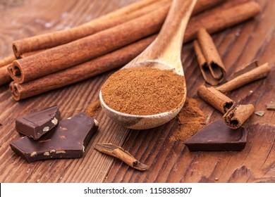 Cinnamon powder on a wooden spoon, cinnamon sticks, and chunks of dark chocolate.