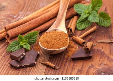 Cinnamon powder on a wooden spoon, mint leaves, cinnamon sticks, and chunks of dark chocolate.