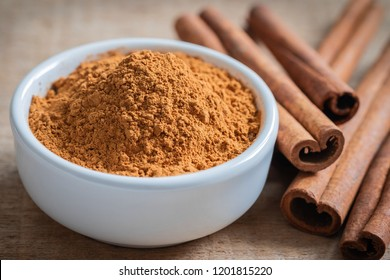 Cinnamon powder and cinnamon sticks on wooden table