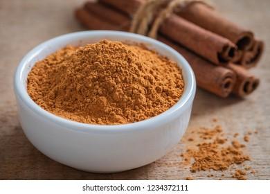 Cinnamon powder and cinnamon sticks on wooden table