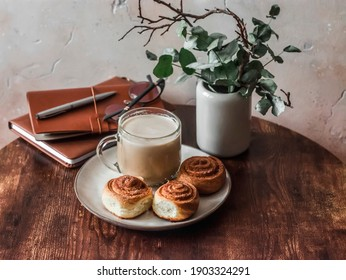 Cinnamon puff pastry buns, cappuccino, vase with decorative flowers, books on a wooden table in a cozy room