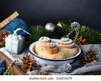 Cinnamon roll buns in enamel bowl with Christmas decorations. Festive treat for holiday breakfast. Copy space