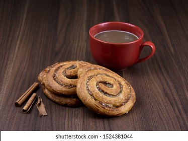 Cinnamon roll and Cup of coffee stock images. Cinnamon roll on a wooden background. Cinnamon roll with spices. Sweet pastry stock images. Favorite Scandinavian pastry. Delicious cinnamon bun