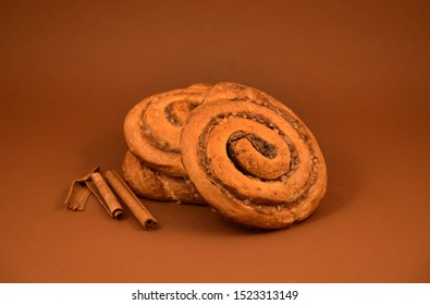 Cinnamon roll on a brown background stock images. Cinnamon roll with spices. Sweet pastry stock images. Favorite Scandinavian pastry. Delicious cinnamon bun stock images