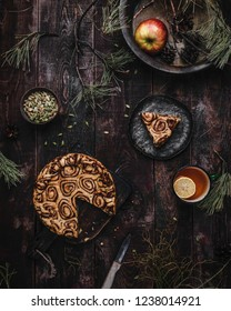 cinnamon roll pie on wooden board with one slice cut, mug of lemon tea, cup of cardamon seeds on wooden table with pine branches
