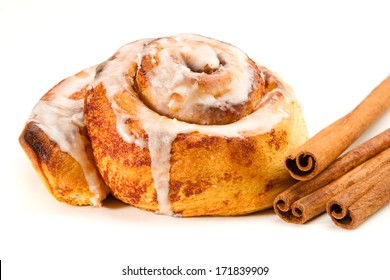 Cinnamon Roll - This is a photo of a tasty cinnamon roll coated in icing and a few cinnamon sticks. Shot with a shallow depth of field on an isolated white background.