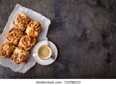 Cinnamon rolls with caramel frosting, pecans and cup of coffee, rustic wooden background. Space for text. Freshly baked homemade cinnamon buns. Sweet cinnamon rolls for breakfast. Top view. Close-up