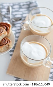 Cinnamon rolls and cup of coffe on white background