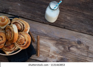 Cinnamon rolls with milk on a wooden table