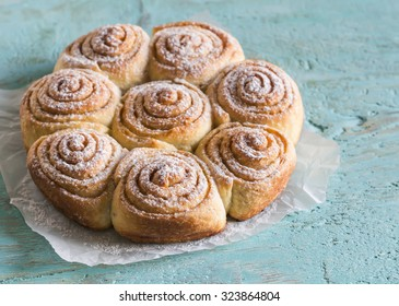 cinnamon rolls on bright wooden surface