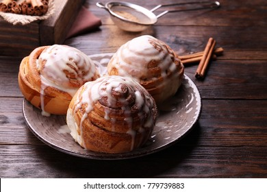 Cinnamon rolls on a plate on a wooden table.Kanelbullens dag