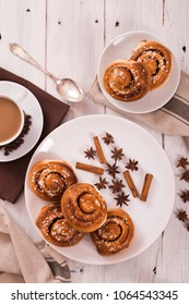 Cinnamon rolls with spices on white dish.