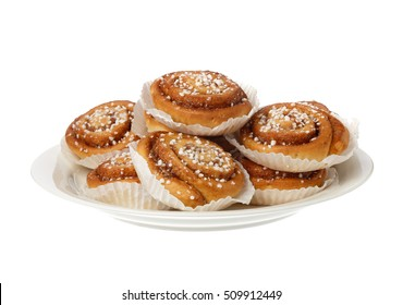 Cinnamon rolls in tins of greaserproof paper isolated on white.