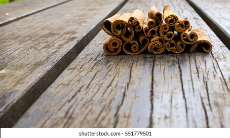 Cinnamon stack on a wooden table. It is a spice obtained from the inner bark of several tree species from the genus Cinnamomum. Cinnamon is used in both sweet and savoury foods. It is mid-brown color