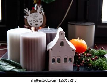 Cinnamon stick, orange, three candlies and ceramic candlestick on dark background. Christmas composition