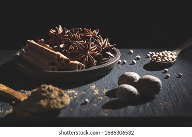 Cinnamon stick, star anise, nutmeg, coriander and ground cumin, on dark background with copy space. Cooking ingredients and condiments concept.