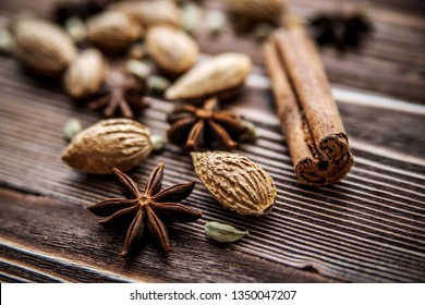 Cinnamon sticks, cardamom, inshell almonds and star anise on a wooden surface.