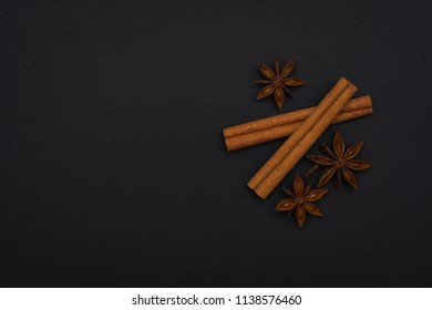 cinnamon sticks and cardamom on a black background top view with copy space for text