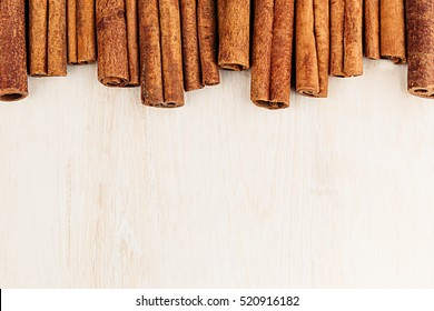 Cinnamon sticks closeup on white wood background. Christmas decorative border of cinnamon sticks spice. Top view.