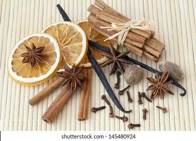 Cinnamon sticks, dried orange, anise stars, nutmegs, cloves and vanilla beans on bamboo background.