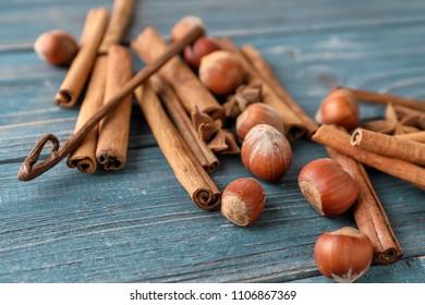 Cinnamon sticks and hazelnuts on wooden background, closeup