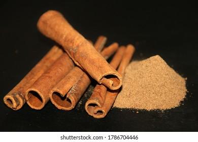Baguettes de cannelle et tas de cannelle sur plaque de pierre noire