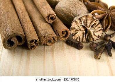 Cinnamon sticks, nutmeg, cloves and anise stars over wooden background