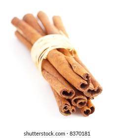 cinnamon sticks on white background tied with raphia