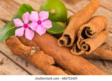 Cinnamon sticks on a wood table with flowers and green lemons in Martinique