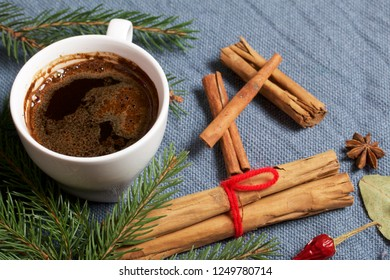 Cinnamon sticks and pods of red pepper next to the fir branches. On a woven background.
