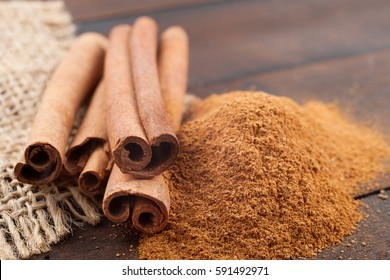 Cinnamon sticks and cinnamon powder on brown wooden board.